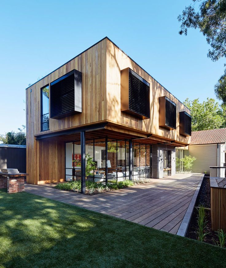 At the rear of this modern house extension, there's an outdoor space for indoor/outdoor living. Black framed windows provide a glimpse of the interior, while a swimming pool provides a place to cool off.