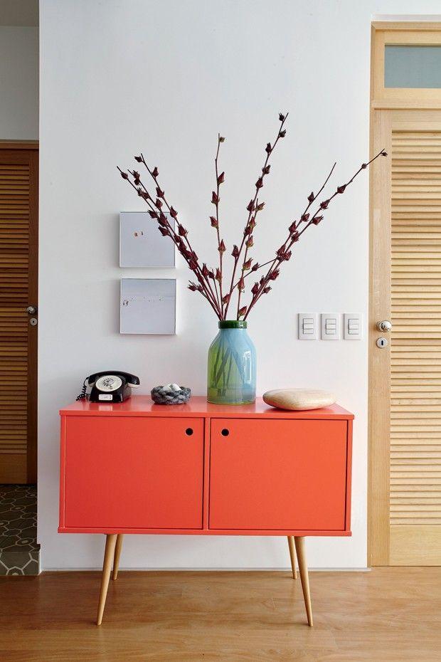 Estar | O armário pé-palito da Desmobilia ganhou laca na cor coral. Vaso e peça de madeira da LS Selection.