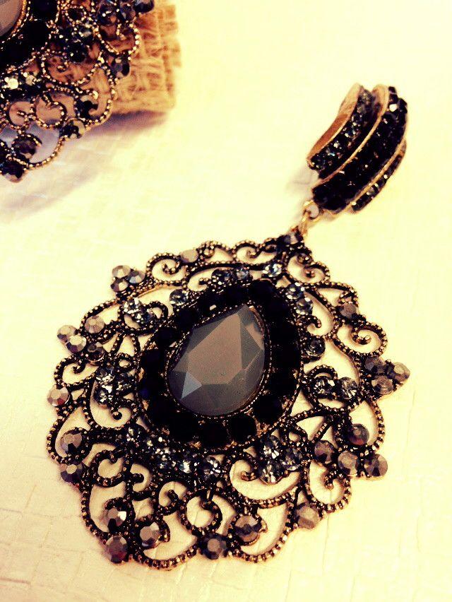 Brinco em bijuteria com acabamento ouro velho e aplicação de cristais nas cores grafite e preta