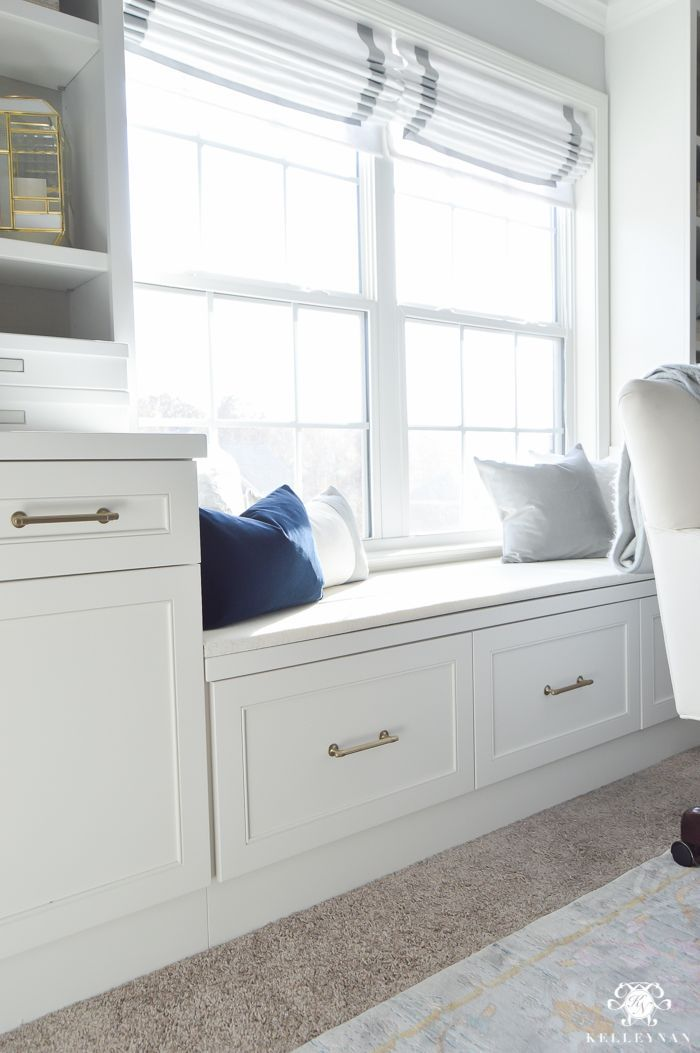 Built-ins in home office with gold cabinet pulls, window seat file drawers, and Roman shades
