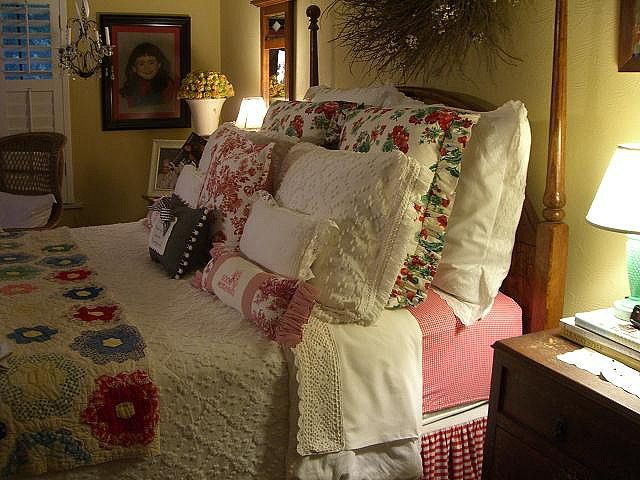 Love the layered pillows, the quilts and the creamy bedspread. Textures! Gold and red. :)