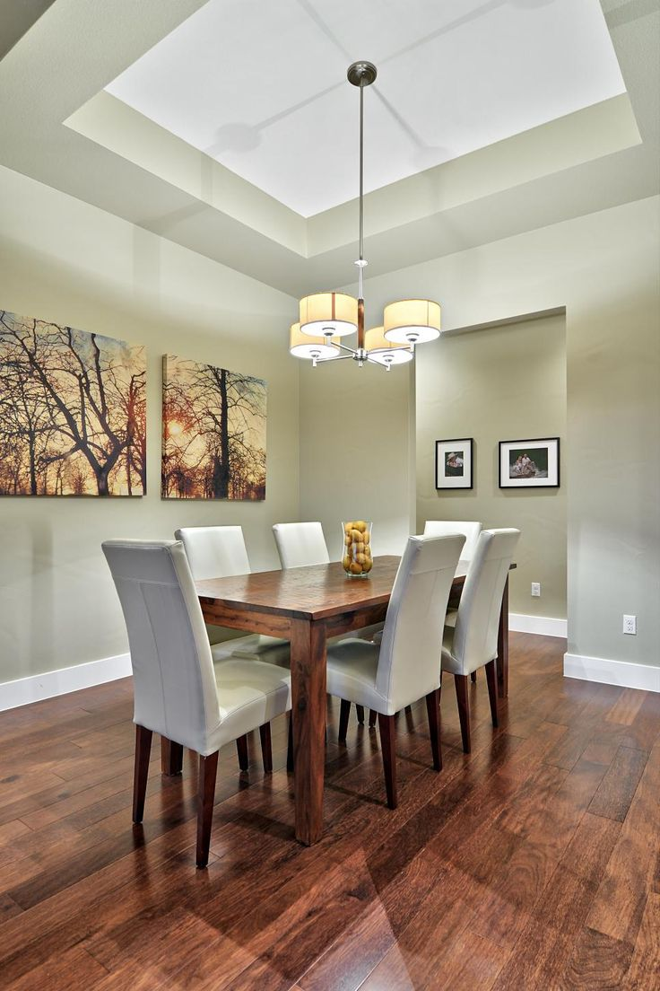 A warm wood dining table pairs with white leather chairs in this transitional dining room. A tray ceiling and gorgeous hardwood floors mix with a contemporary chandelier and wall art.