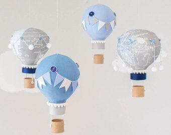 Bebé de globo pastel aire caliente móvil en telas menta, Aqua, rosa y amarillo. Las fotos muestran 4 globos de aire caliente flotando las nubes puffy bajo dos. Cada globo es hecho a mano de varias telas coordinación y adornado con banderas diferentes del empavesado, panaderos de la guita, botones, pompones y canastitas, impresos con tecnología 3D, le dan un aspecto real de mimbre. Cuelgan de un móvil de madera con dos cadenas de banderas pequeñas del empavesado. Puede personalizar una de las…
