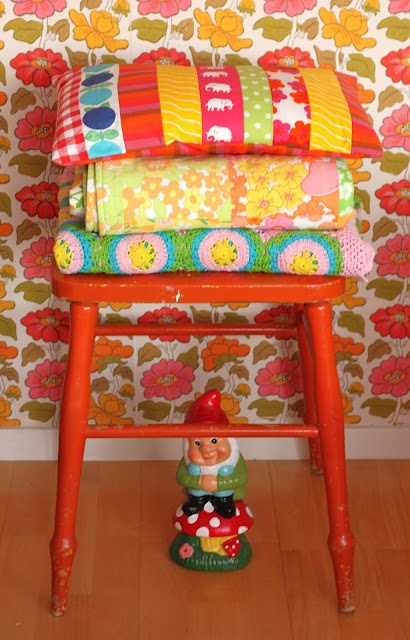 I love these vintage bedding and pillows on the red stool! And also... how could i miss that fabulous wallpaper?!