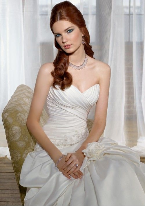 This custom made satin a-line wedding gown features strapless sweetheart neckline, elegant applique accents, lace up rouched bodice and pick-up skirt with hand-made flower accents finishing this fabulous style with chapel train. Please be kindly informed that this dress cost excludes any accessories like petticoats, gloves, veils, jackets, crowns, necklaces and so on.