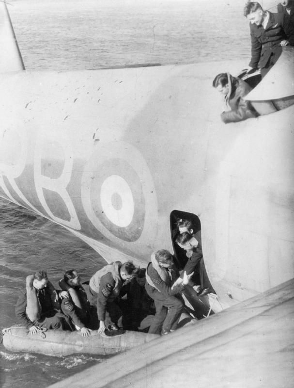 The crew of an Armstrong-Whitworth Whitley of Coastal Command, which had come down in the Atlantic, being rescued by a Short Sunderland of No. 10 Squadron RAAF. The six crew are clambering into the Sunderland from a two-man dinghy, which they were forced to use after their main dinghy failed to function. The photograph was taken from the wing of the Sunderland by one of its crew.