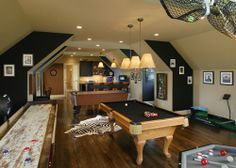 This attic game room has it all: bar, air hockey, shuffleboard, pool table, and more...