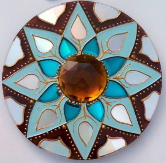 Mandala feita em CD reciclado. Tamanho de 12cm de diâmetro. Pintura vitral, decorada com pedra acrílica e tinta relevo dourada. Com gancho de metal para ser pendurada na parede. As mandalas aéreas podem ser penduradas em todos os ambientes, mas são colocadas especialmente nas sacadas, varandas ou perto de janelas. As cores são muito utilizadas no Feng Shui. Elas irradiam nos ambientes determinadas curas, pois cada cor vibra em determinada freqüência, mesmo que não possamos perceber. Este é…