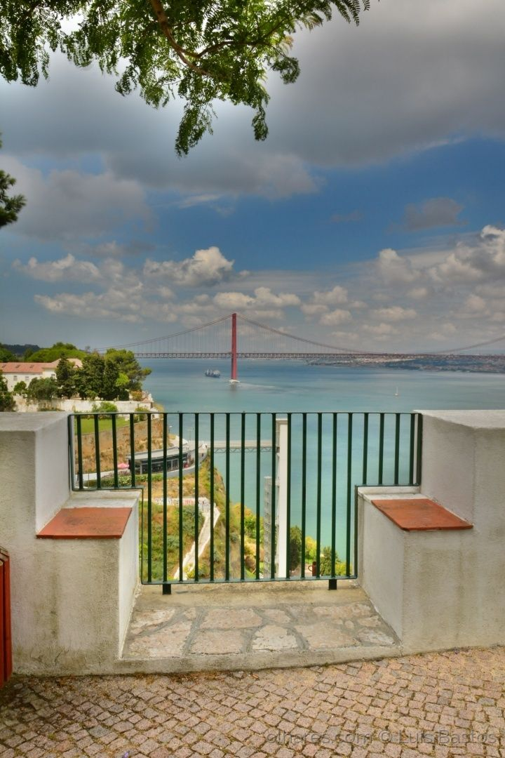 Fotografia tirada no Miradouro do Castelo, Almada. É possível ver Lisboa, o Rio Tejo e mais adiante a barra do Tejo, a ponte 25 de Abril, o Elevador Panorâmico da Boca do Vento
