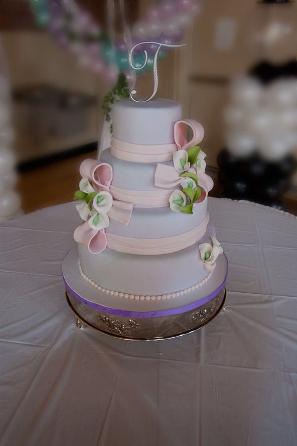 A pink and lavender wedding cake with sugarpaste bows and Calla lilies.  German chocolate, pumpkin spice and other wonderful flavors.