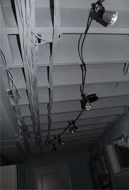 Wires fade into the background with paint.  Painted basement ceiling w/ track lighting