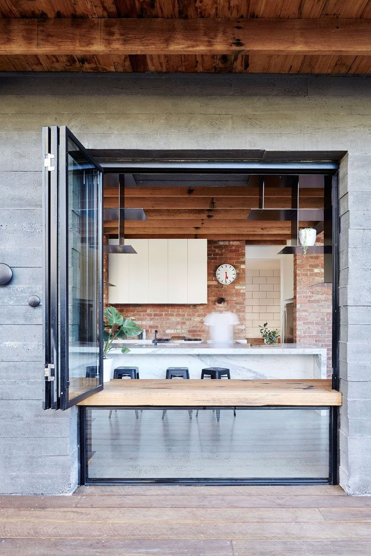 Exposed concrete surrounds a window with a wood ledge and when the window is open, it can be used as a counter or desk.