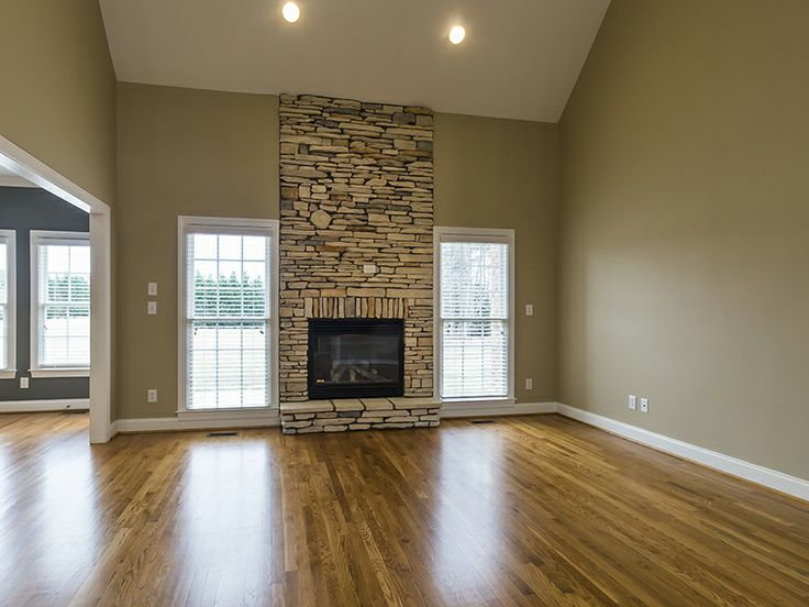Floor to ceiling stacked stone fireplace flanked by windows.