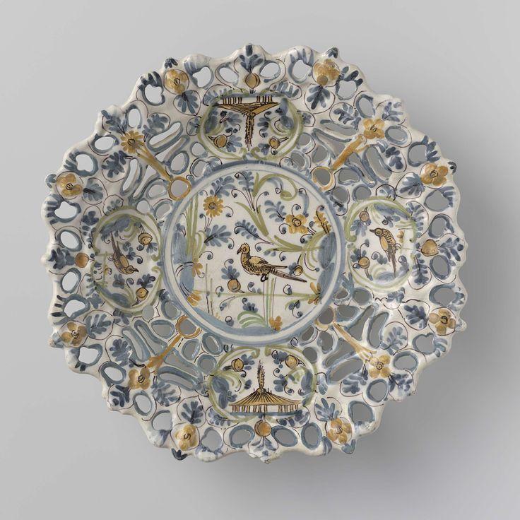 Anonymous | Schaal met opengewerkte rand. Op plat versierd met een vogel tussen takken, omgeven door een cirkel., Anonymous, c. 1650 - c. 1680 | Ronde schaal van veelkleurig beschilderde faience. In het midden is een cirkel waarbinnen een vogel tussen takken geschilderd. Op de brede opengewerkte rand zijn vier ovalen geschilderd. In twee ovalen is een huis geschilderd en in twee ovalen een vogel. De schaal is gemerkt.