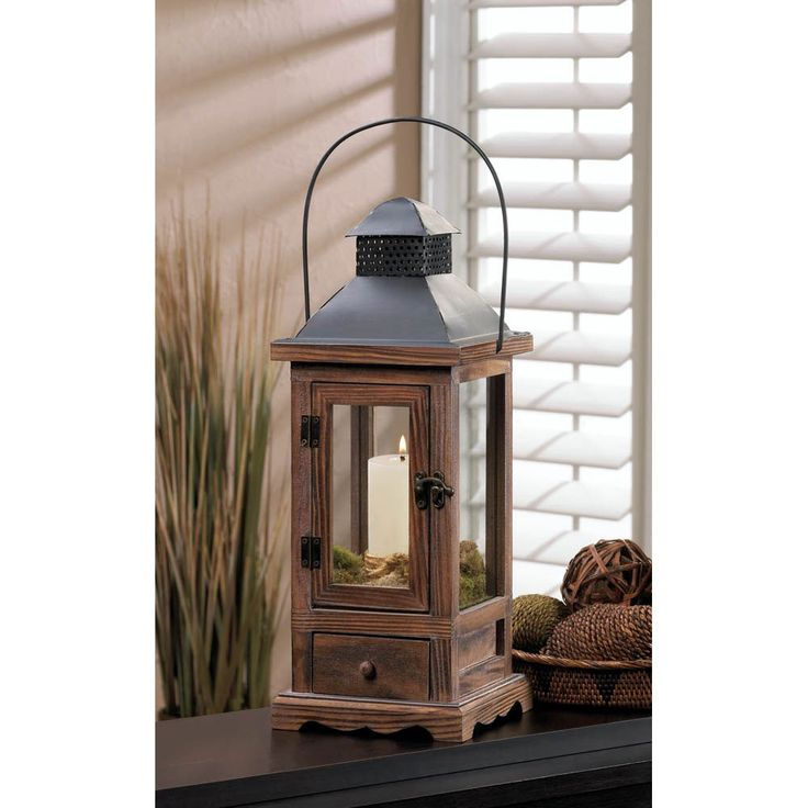 Light up your nights with this small lantern that's big on charm. The wooden framework gives way to a black metal roof with a hanging handle, and below is a neat pullout drawer. Candle not included.