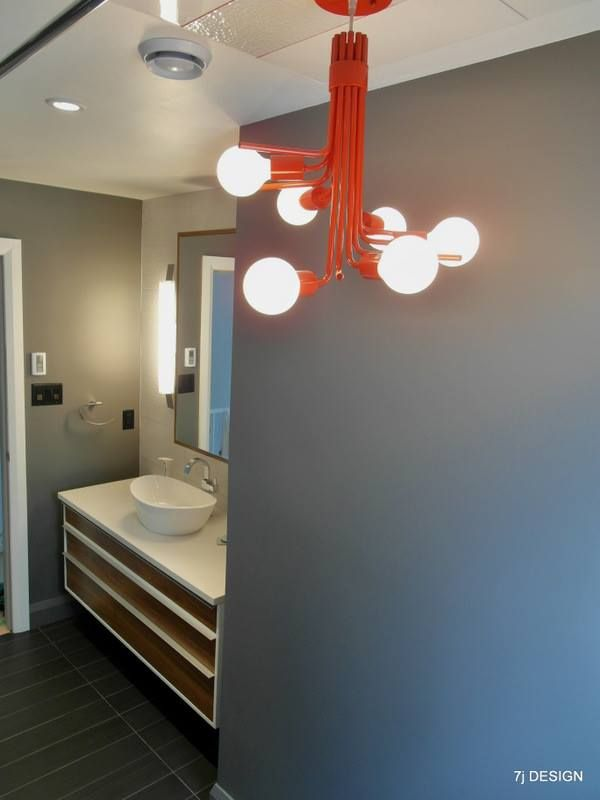 This 1980s home was overhauled with a new and modern bathroom.  Greys and whites were accented by a sculptural red light fixture.