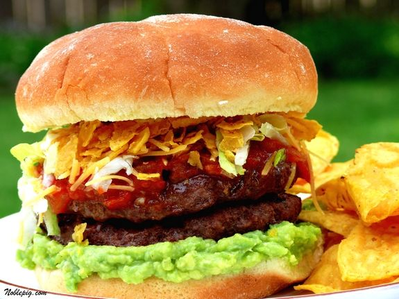 Taco Burger--Ground oregano  Ground cumin  Chile powder  Guacamole  Sour cream  Cheddar cheese, shredded  Lettuce, shredded  Salsa  Tortilla chips  Burgers (your favorite recipe)  Hamburger buns