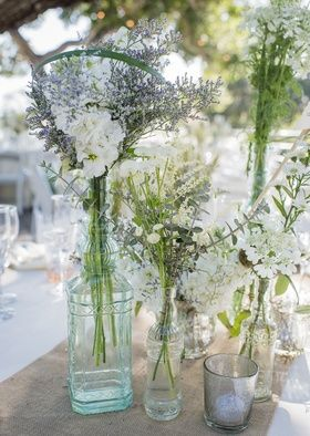 Wildflower Arrangements in Glass Vases on Rustic Table Runner | Photography: Willa Kveta Photography. Read More:  http://www.insideweddings.com/weddings/romantic-outdoor-bohemian-chic-wedding-at-a-santa-barbara-park/755/