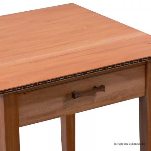 Closeup of the front of the table showing the banding and handle