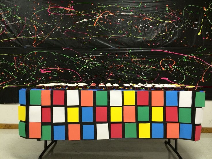 Black tablecloth with splattered acrylic paint as backdrop for cake table...rubrics cube as table skirt for 80's themed birthday party