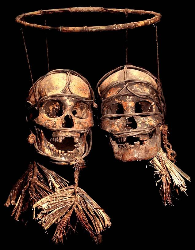 DAYAK TRIBE:  TWO HANGING BOUND AND DECORATED  HEADHUNTED HUMAN TROPHY SKULLS  HUMAN BONE, VEGETABLE MATTER, FIBER, BAMBOO  THE DAYAK TRIBE, FROM BORNEO ISLAND  INDONESIA, CARVE DESIGNS INTO THE SKULLS  OF THEIR HEADHUNTED VICTIMS AND INSERT WOODEN FIGURES.