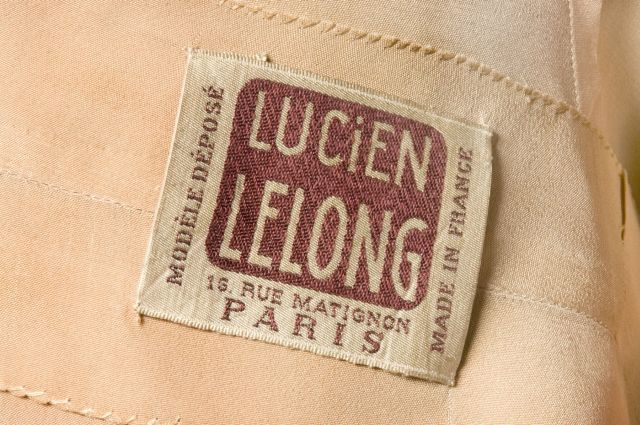 """Lucien Lelong label. He was a French couturier who was prominent from the 1920s to the 1940s. Lelong did not actually create the garments that bore his label. """"He did not design himself, but worked through his designers,"""" wrote Christian Dior, who was a member of the Lelong team from 1941 until 1946, during which time he created the collections in collaboration with Pierre Balmain."""