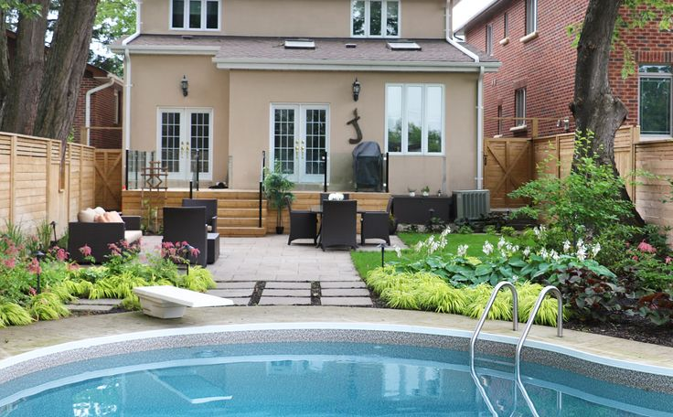 Lush gardens frame up this Banas natural stone patio and cedar deck with glass railings