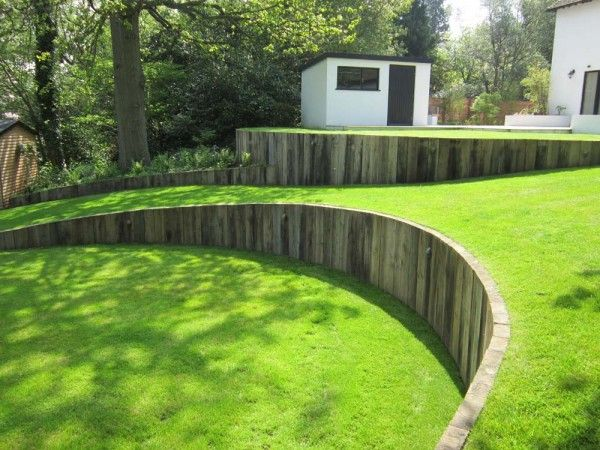 Curved timber retaining wall with vertical railway sleepers, great against a lawn. Very low maintenance