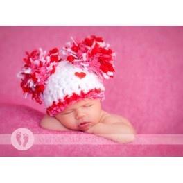 Suave gorrito con dos pompones en distintas texturas y colores (rosa, rojo y blanco). Incluye botón de corazón.