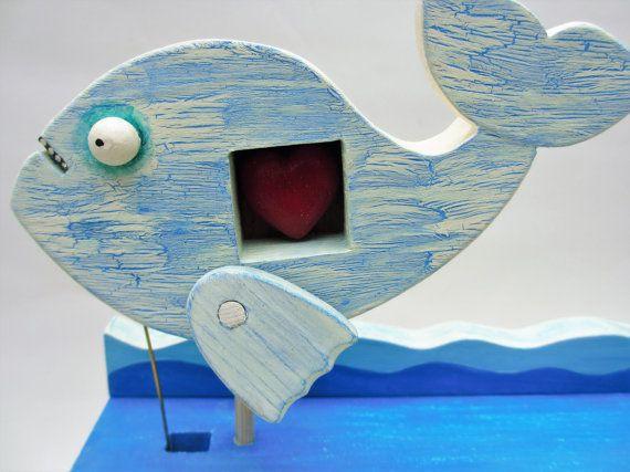 Cuando la manija se da vuelta el pescado grande con gracia nada mientras menea los peces más pequeños a lo largo de un poco menos agraciado detrás.  Esta pieza ha sido hecho a mano en madera y luego pintada por mí con una mirada de efecto leve resistido o desgastado pintura en la parte superior de la caja de la mano. Luego he aplicado un barniz a la pieza para sellar y proteger el acabado.  Nota: esto se hace como una obra de arte coleccionable. NO es un juguete y por lo tanto inadecuado…