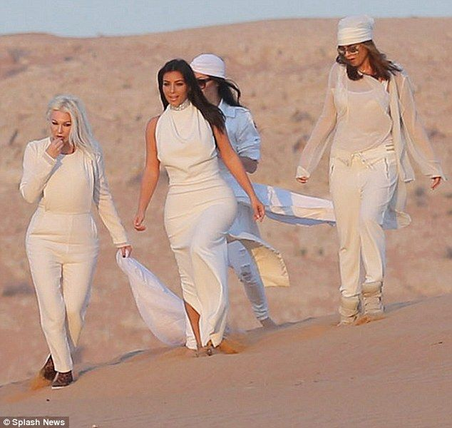 Dramatic sight: Kim Kardashian and her beauty team wore all-white as they strolled through the desert in Dubai last week