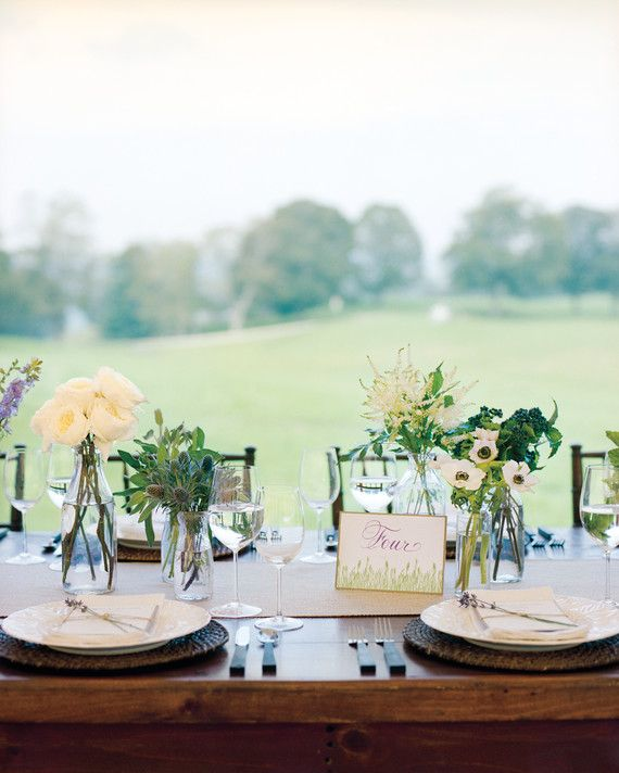 Vintage glass bottles, each filled with a single type of flower—garden roses, dahlias, privet berries, delphinium, Queen Anne's lace, astilbe, or anemones—lended a pastoral look to wooden tables in Reading, Vermont.
