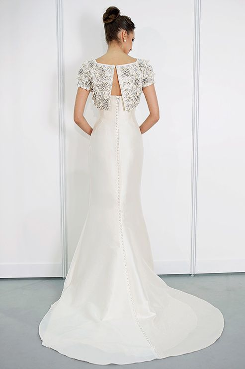 Beaded bolero tops a long row of buttons down a Rafael Cennamo wedding gown, Fall 2013. Click to see the front of the dress.