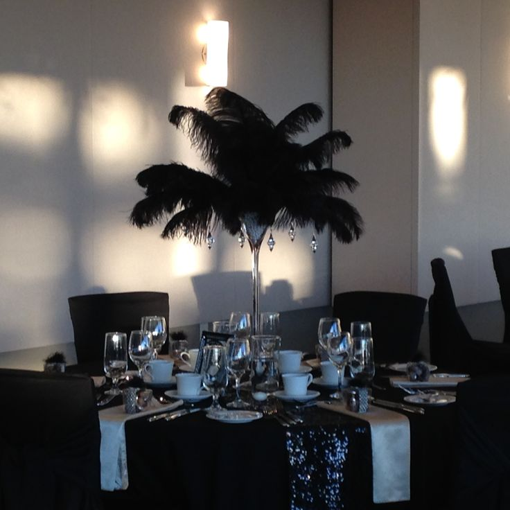 Dramatic black ostrich feather centerpiece. Pearl accents. Black and gold theme