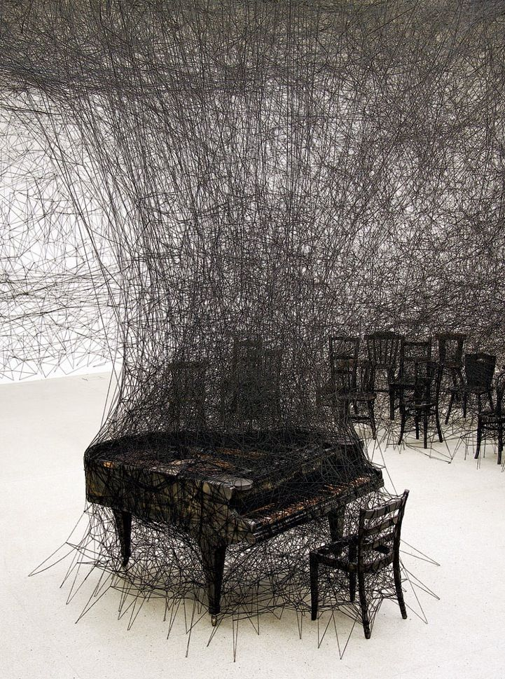 Artist uses black thread woven throughout a room in attempt to translate her memories of her neighbours house (and piano) being scortched in a fire when she was a child.
