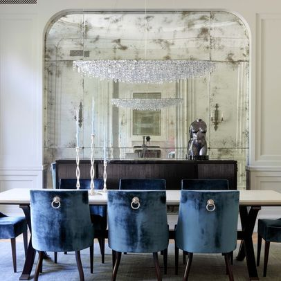 antique mirror wall in a dining room adds drama and the use of mirrors