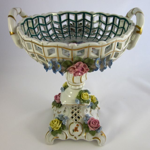 SANDIZELL is well-known for its ceramic lace figurines. This comport is elaborately decorated with applied porcelain roses and forget-me-nots. The latticed interior has a beautiful spray of Dresden flowers or Deutsche blumen. Light shines through the pierced body making it especially attractive when seen from above. The delicacy and playfulness of the rococo style offers visual contrast in a simple modern setting. 50% discount Nov. 25-29 #MusesAntiques #RubyLane