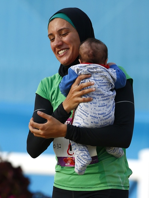 Egypt's Aya Medany carries a baby after the end of the women's modern pentathlon during the London 2012 Olympic Games August 12, 2012.  REUTERS/Darren Staples (BRITAIN  - Tags: OLYMPICS MODERN PENTATHLON SPORT)