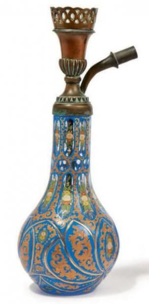 NARGUILÉ AVEC UNE COLONNE OTTOMANE en métal ajouré et gravé. Le vase en verre de Bohême taillé à décor polychrome et doré de eurettes et rinceaux. Bohême, 19esiècle Haut: 35 cm A NARGHILE WITH A METALLIC OTTOMAN ELEMENT ON A NICE BOHEMIAN GLASS VASE 19ThCENTURY