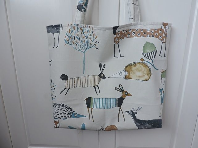 A querky tote bag, shopping bag, craft bag  made with  cotton duck fabric depicting characature woodland animals in grey, turquoise and tan on a cream background. Fully lined in a pale grey and white cotton fabric. It has a squared off bottom to the...