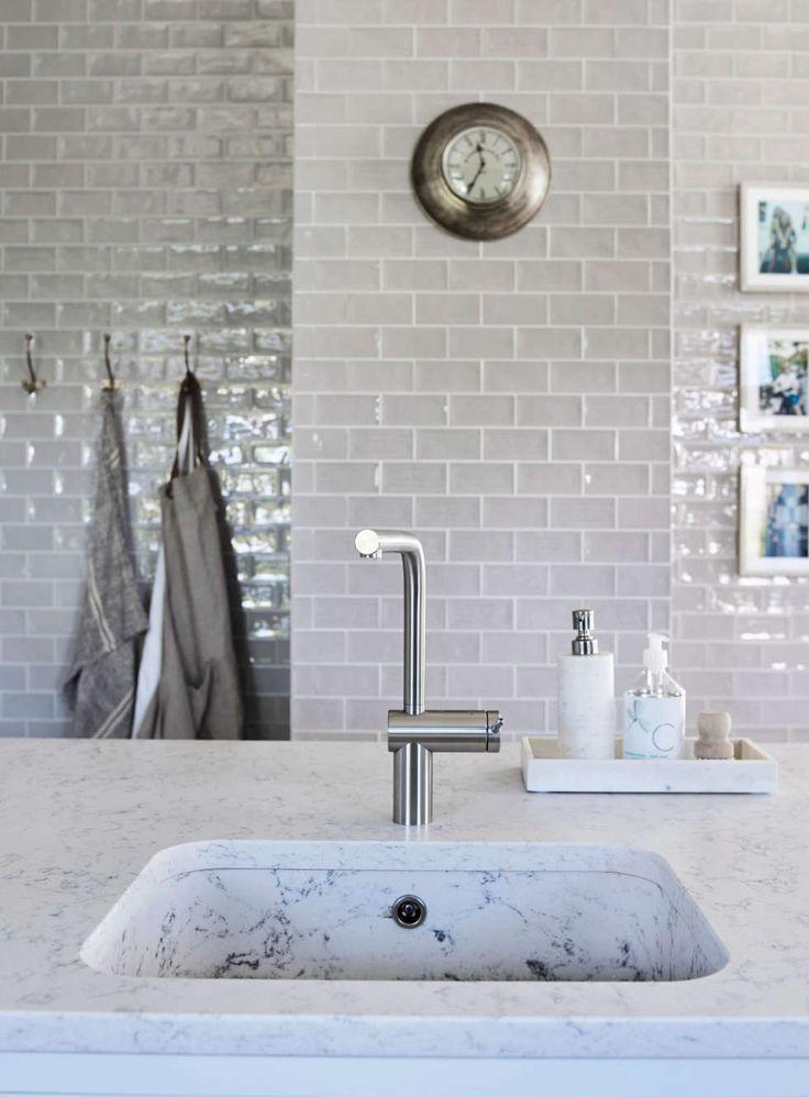 KJØKKENØY: Kjøkkenøya har vask og benkeplater i Silestone som er solide steinplater, denne varianten minner om marmor, men er langt mer hardfør. De lyse, blanke flisene på veggen er håndlagde, også fra L-Flis og Interiør, fagflis.no.