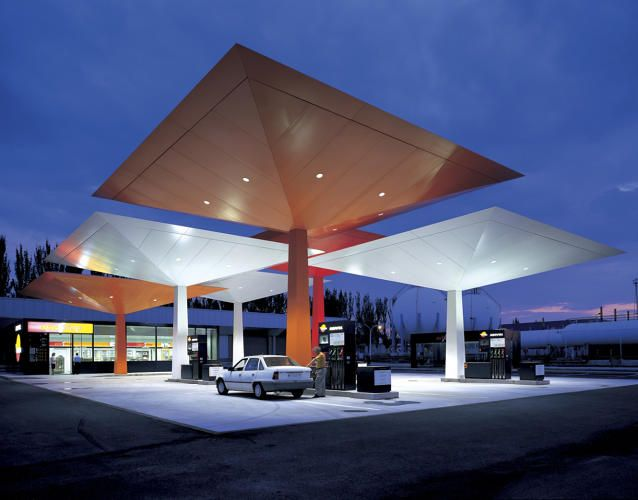 7 | 9 Gorgeous Gas Stations Throughout History | Co.Design | business + design. In 1997, Spanish oil company Repsol commissioned starchitect Norman Foster to come up with a gas station model that could be used across 200 sites in Spain. Foster's modular canopy system in Repsol's signature colors is a flexible enough design to be applied to a variety of site conditions. The number, height, and amount of overlap of these vivid umbrellas varies, but the stations remain easily recognizable even…
