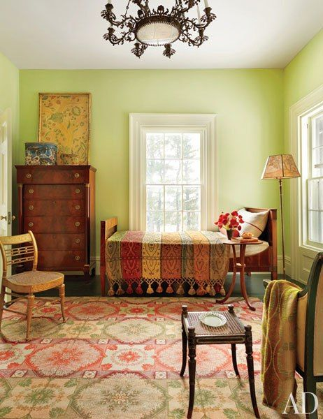 A guest room in this upstate New York home, painted in a Farrow  Ball green, contains a 19th-century chandelier, a French Empire chest and bed, and an American fancy chair from the same period.