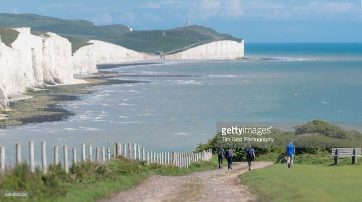 A group of hikers with a dog walking down a dirt track with the Seven Sisters chalk cliffs and Belle Tout Lighthouse in the distance.