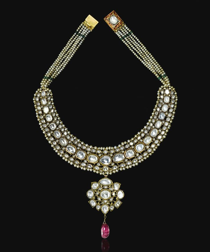 A gem-set and enamelled gold necklace, North India, 19th century comprising facet-cut white sapphires set in gold with foil backing, on flexible openwork chain surrounded by seed-pearl borders, hanging flowerhead-shaped pendant with spinel drop, enamelled on the reverse in red, green and white with floral details on each setting, rows of pearl-strings leading to square clasp 32.5cm. max. unclasped 20.5cm width.