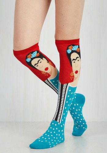 Express your fiercely creative spirit by donning these Frida Kahlo socks! This long cotton-blend pair depicts the infamous Mexican painter and feminist icon in intarsia knit with her trademark full eyebrows and flower-adorned up-do against a red backdrop, her teal-blue polka dot shirt blending into the heel and foot of each sock. Wear them with a casual frock and a draping cardigan, and let this bright pair and Kahlo's artistic oeuvre inspire your imagination!