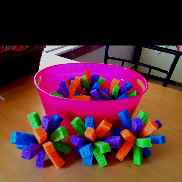Water fight sponges  I got 4 (4 packs) of sponges. I used the ocello brand because they were so colorful.  Open 1 pack and cut each sponge into 4 strips long ways.  Then bunch 8 strips together and tie in the middle with string or ribbon... And that's it. I got 8 out of 16 sponges. Get a bucket of water and let the kids go crazy throwing them at each other!  I like this because there's no balloon pieces to pick up after a water ballon fight!