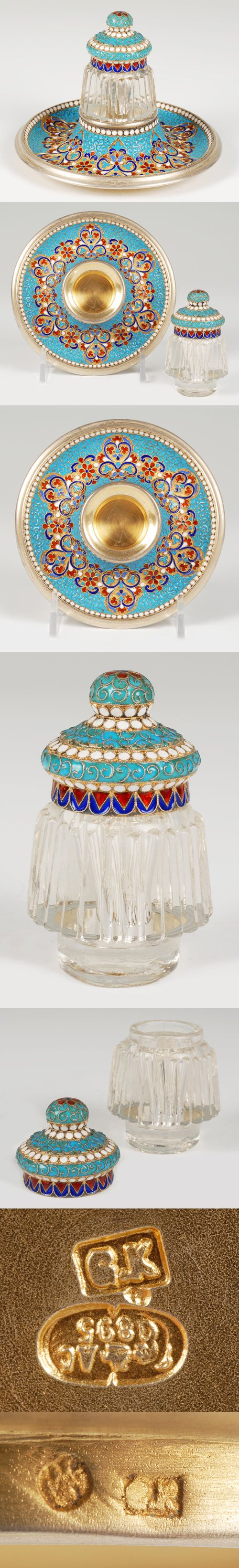 A Russian glass, silver gilt and cloisonne enamel inkwell made by Gustav Klingert, Moscow, circa 1895. Of tapering form, the glass inkwell's lid decorated with scrolling filigree wires against a turquoise ground bordered by white enamel beads, the stand similarly decorated.