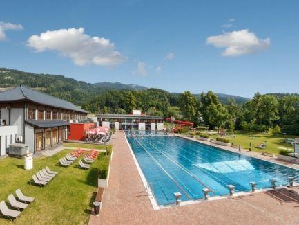 Blick auf den weitläufigen Freibereich im Asia Spa Leoben: 50-Meter-Sportbecken, Freizeitbecken mit Röhrenrutsche, Sprungturm, Sonnenterrasse und Liegewiese