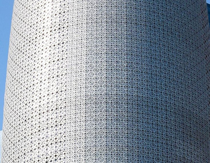 The multi-layered patterns adorning the facade evoke ancient Islamic screens designed to shade buildings from the sun.